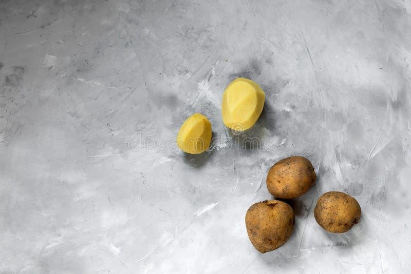 Grandi tuberi sbucciati e non sbucciati della patata bugia su un fondo grigio immagini stock libere da diritti