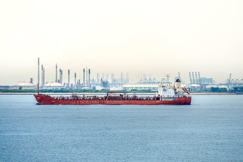 Grandi vele colorate rosse dell'autocisterna del guscio lungo il costiero del porto di industria con la grande azienda agricola d fotografia stock