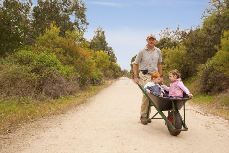 Grandkids de passeio do avô no wheelbarrow fotografia de stock royalty free