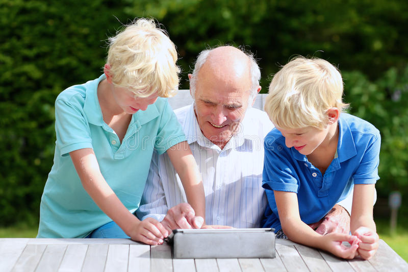 Grandkids enseignant le grand-papa à utiliser le PC de comprimé images stock