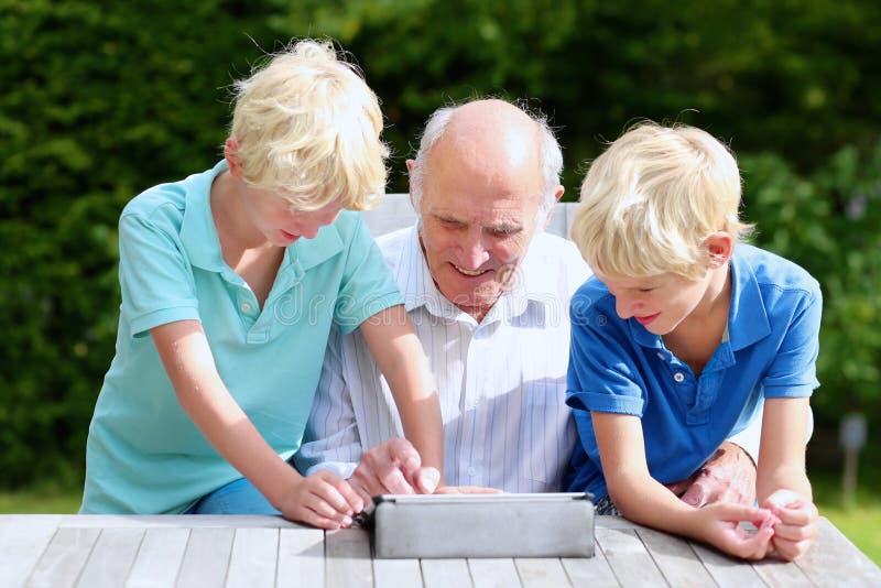 Grandkids som undervisar morfadern att använda minnestavlaPC arkivbilder