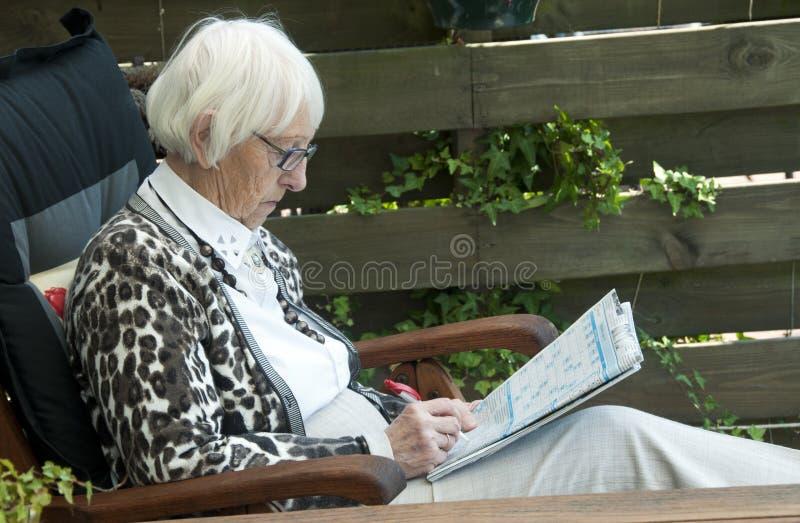 Grandm che risolve puzzle immagine stock