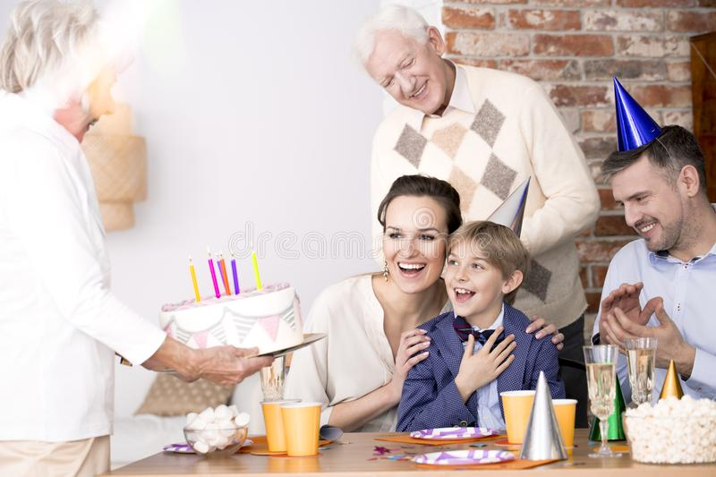 Grandma bringing birthday cake to a party royalty free stock photo