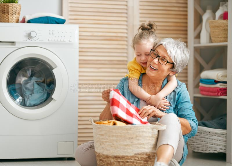 Grandma and child are doing laundry. Happy grandma and child girl little helper are having fun and smiling while doing laundry at home stock photography