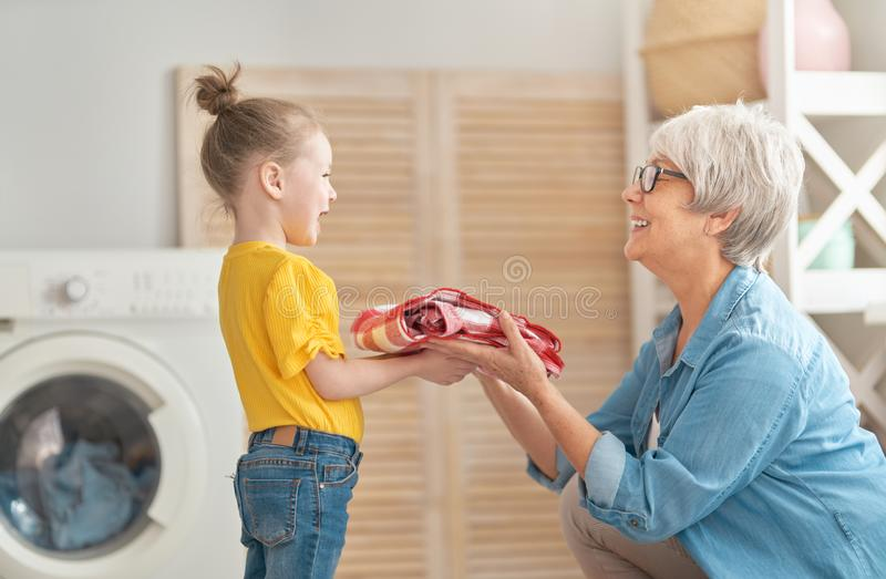 Grandma and child are doing laundry. Happy grandma and child girl little helper are having fun and smiling while doing laundry at home royalty free stock photography