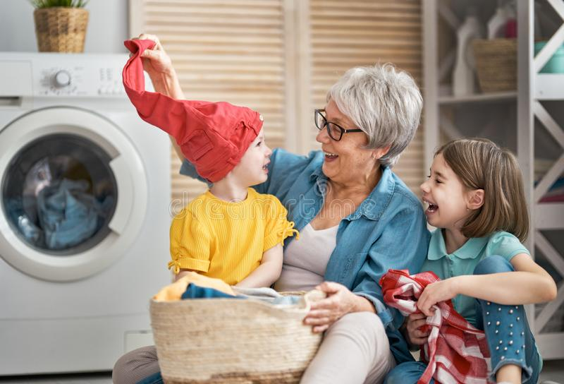 Grandma and children are doing laundry stock photography
