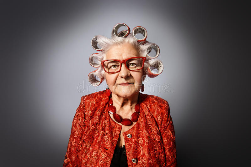 Grandma with curlers. Portrait of an elderly woman in curlers looking at camera royalty free stock images