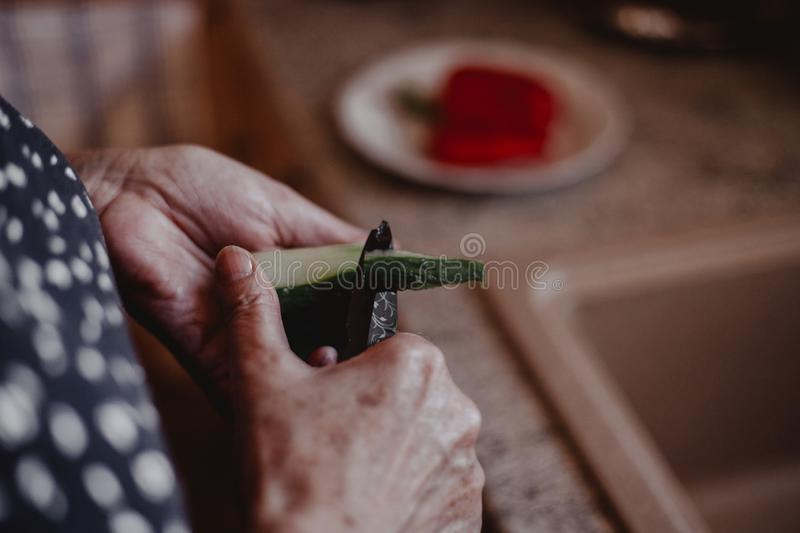 Grandma cutting healthy vegetables in kitchen royalty free stock photography