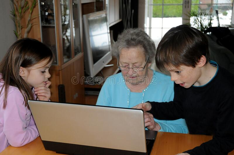 Grandma gets a lesson in computer operation. Grandchildren use the quarantine time during the Corona crisis to teach their grandma how to work on the computer stock photos