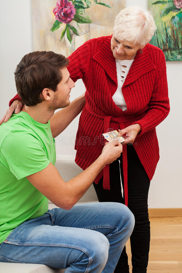 Grandma giving money to her grandson royalty free stock photography
