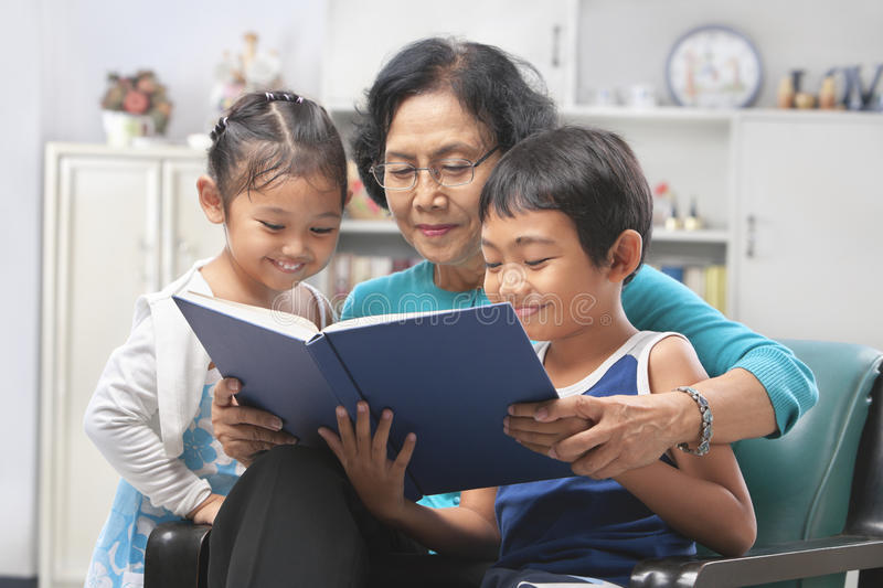 Grandma and grandchildren reading book together stock photos