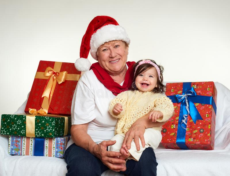 Grandma and granddaughter dressed in santa hat with gift boxes sit on sofa, white background. New year eve and christmas holiday c stock photos