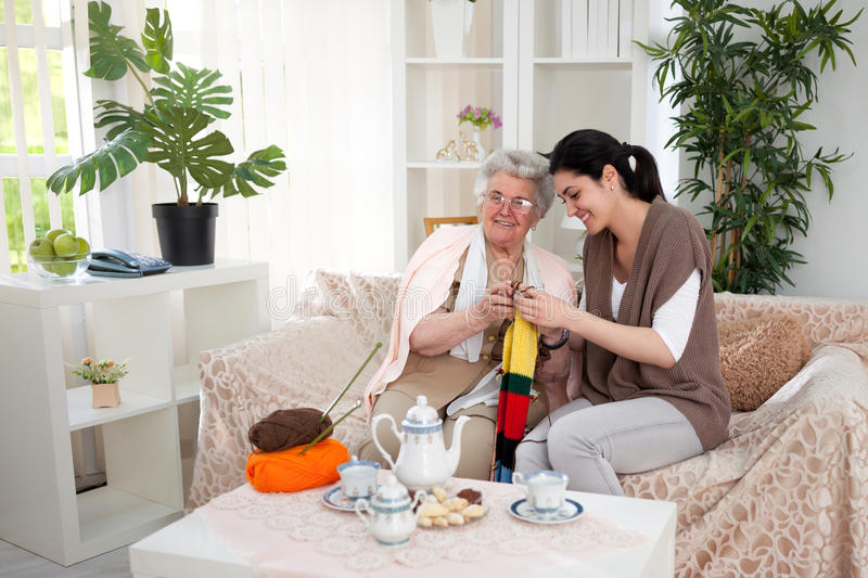 Grandma and granddaughter having a knitting time` stock photo