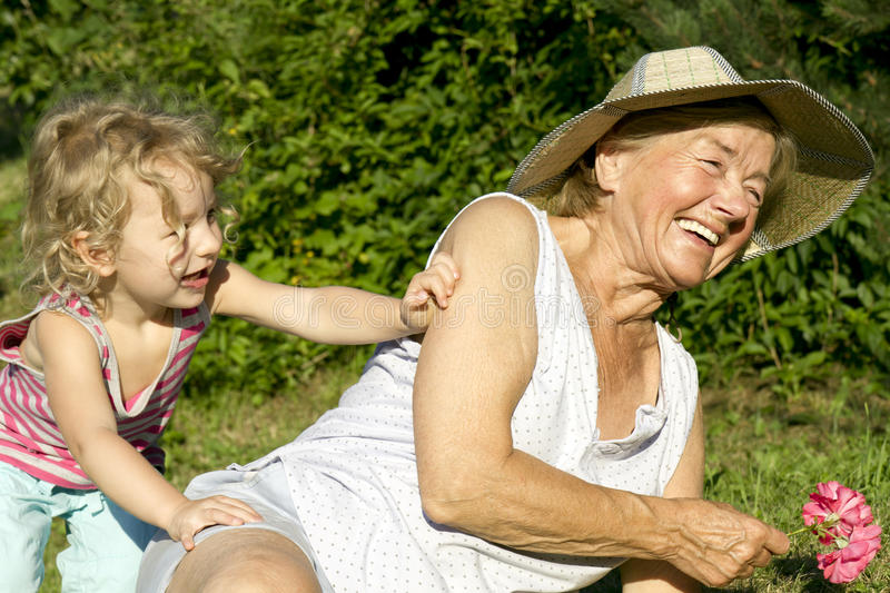 Grandma and granddaughter play in garden