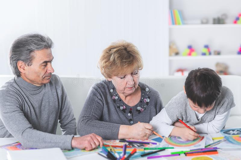 Grandma and grandpa are drawing a rainbow with their grandson stock image