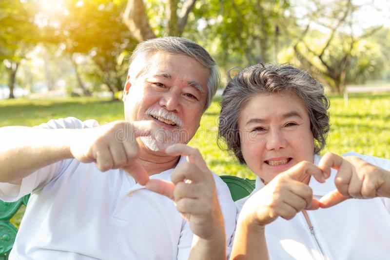Grandma and grandpa or grandparents make symbol of love by using hands and fingers for making hearts. Lovely older couple or. Senior people love each other for royalty free stock photography