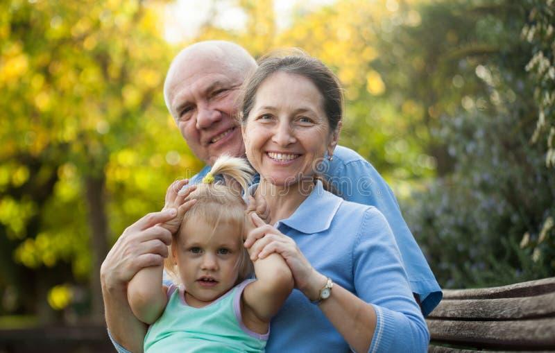 Grandma and grandpa with little grandaughter stock photo