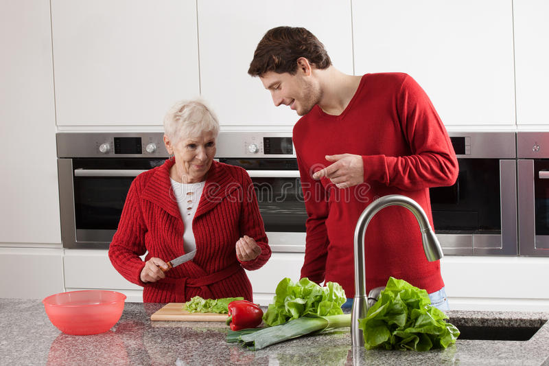 Grandma and grandson cooking. Happy grandma is preparing meal at kitchen witch grandson royalty free stock photos