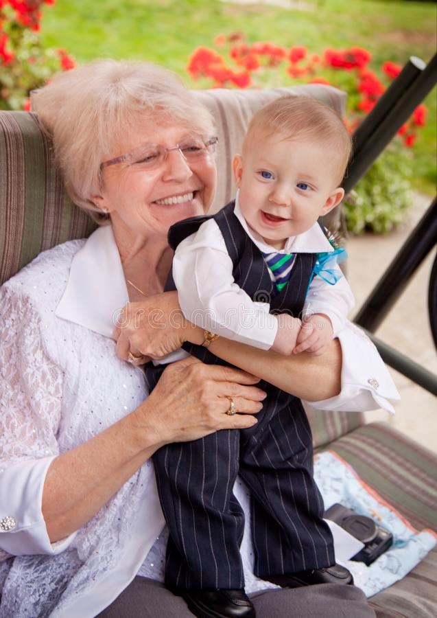 Grandma with grandson. Grandma holding grandson in a fancy suit royalty free stock photo