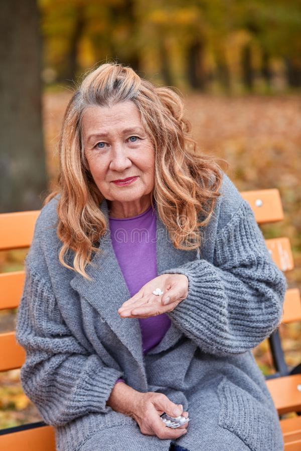 Grandma is going to drink pills in her hand in the autumn park stock photos