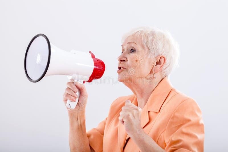 Grandma with megaphone. An elegant grandma talking through a megaphone royalty free stock photography