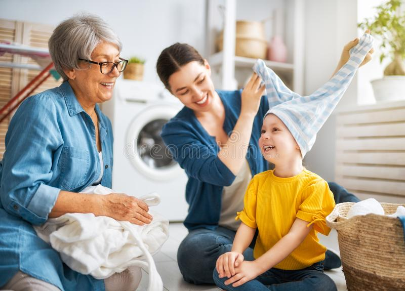 Grandma, mom and child are doing laundry royalty free stock photography