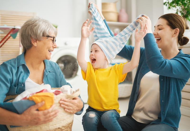Grandma, mom and child are doing laundry stock photo
