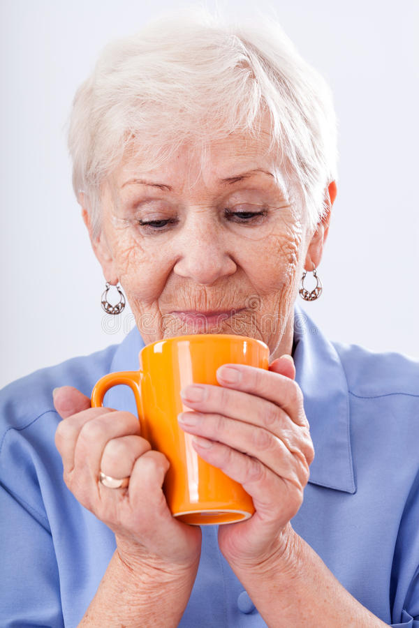 Grandma with mug. A grandma with a hot drink in an orange mug stock photo