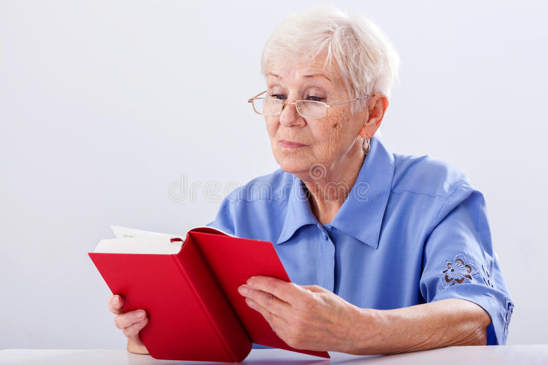 Grandma reading book. A grandma in glassed reading a red book royalty free stock image
