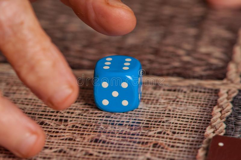 Grandma rolls a blue dice.Social game. Throwing a blue cube royalty free stock photo