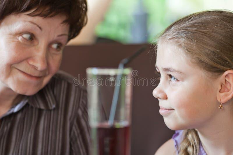 Grandma smiling to her granddaughter stock images