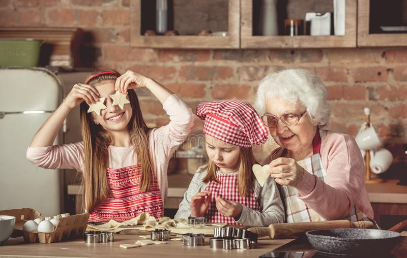 Grandma teaching granddaughters to bake cookies. Grandma teaching granddaughters to bake homemade cookies. Little girl holding two star-shaped cookies in front royalty free stock photography