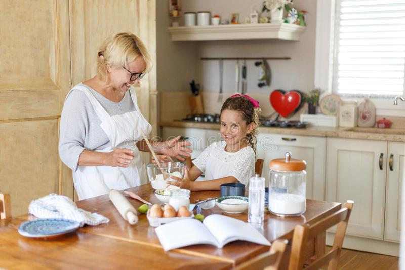 Grandma in white apron with cute curly granddaughter spend wonderful time in the kitchen, smiling and there are happy. stock photo