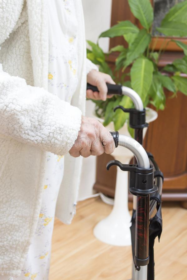 Grandma in a white bathrobe. Wrinkled hands of a very old woman hold the handles of the walker handle. stock image