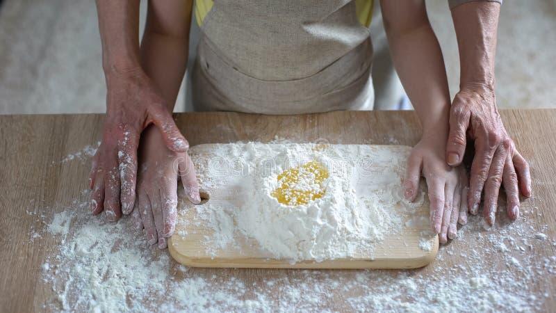 Grandmom die zorgvuldig kleindochter het kneden deeg, familierecept, het koken onderwijzen stock foto's