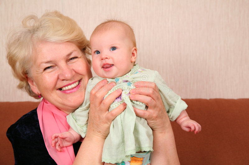 Grandmother with baby. On a sofa royalty free stock images