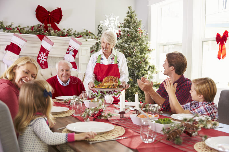Grandmother Bringing Out Turkey At Family Christmas Meal royalty free stock photography
