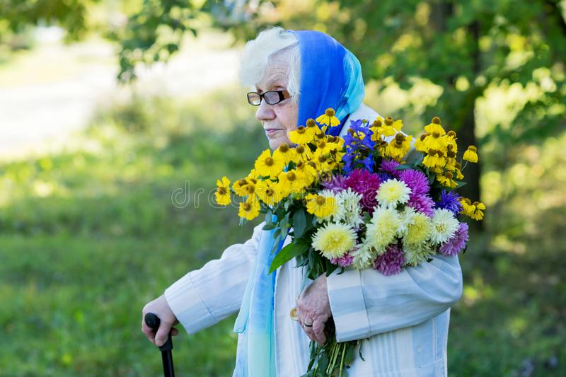 Grandmother with a cane and flowers. On the background of trees royalty free stock photo