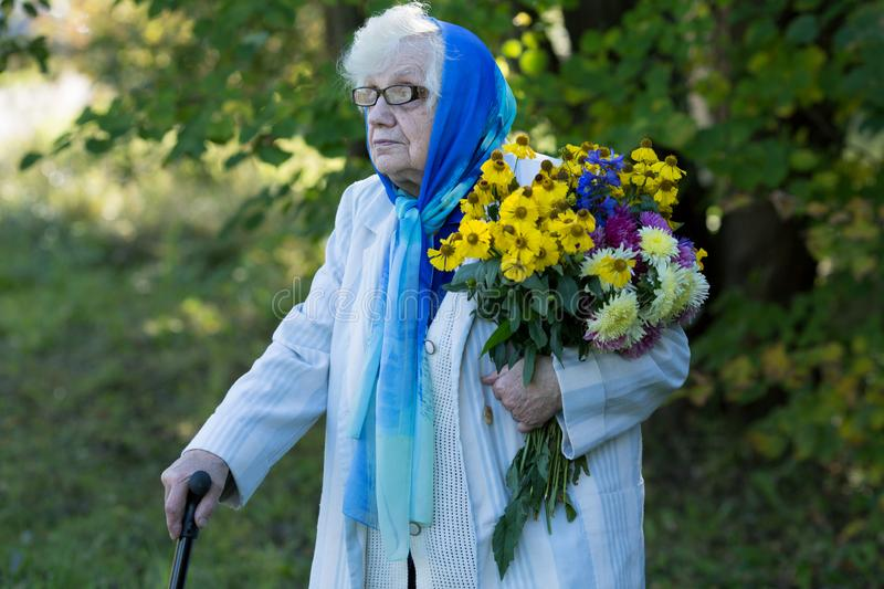 Grandmother with a cane and flowers. On the background of trees stock photos