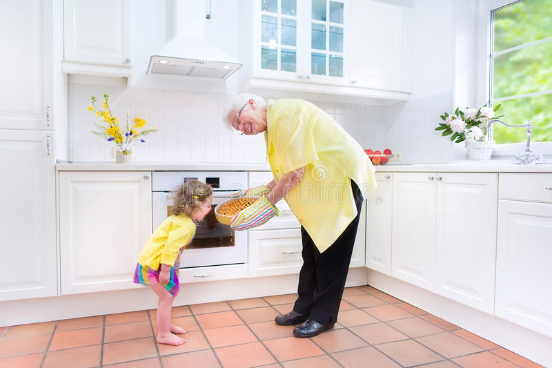 Grandmother and charming girl baking pie in white kitche. Happy beautiful great grandmother and her adorable granddaughter, curly toddler girl in colorful dress royalty free stock photo