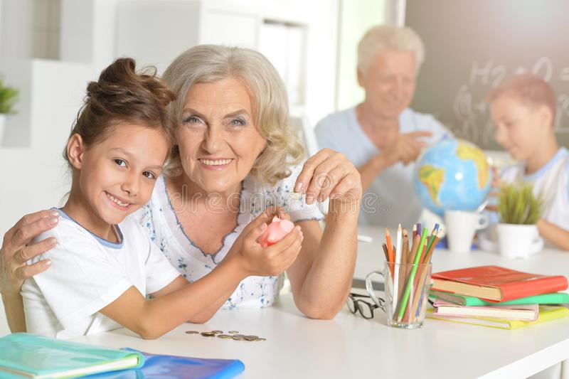 Portrait of grandmother and child daughter putting coins. Grandmother and child daughter putting coins into piggy bank royalty free stock image