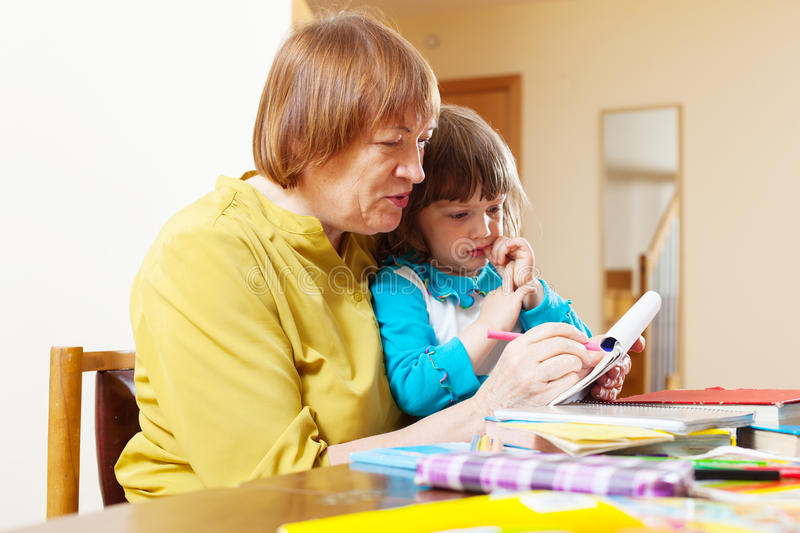 Grandmother and child drawing on paper. At home interior. Focus on woman royalty free stock photography