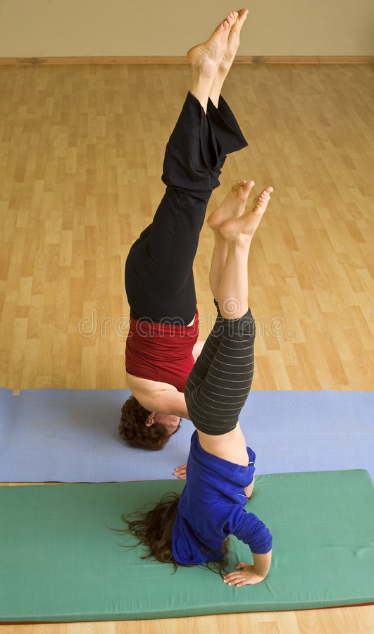 Grandmother and child exercising. Doing a headstand together stock images