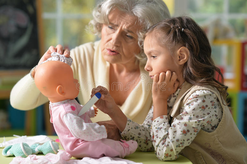 Grandmother and child play. Portrait of grandmother and child play with baby doll stock images