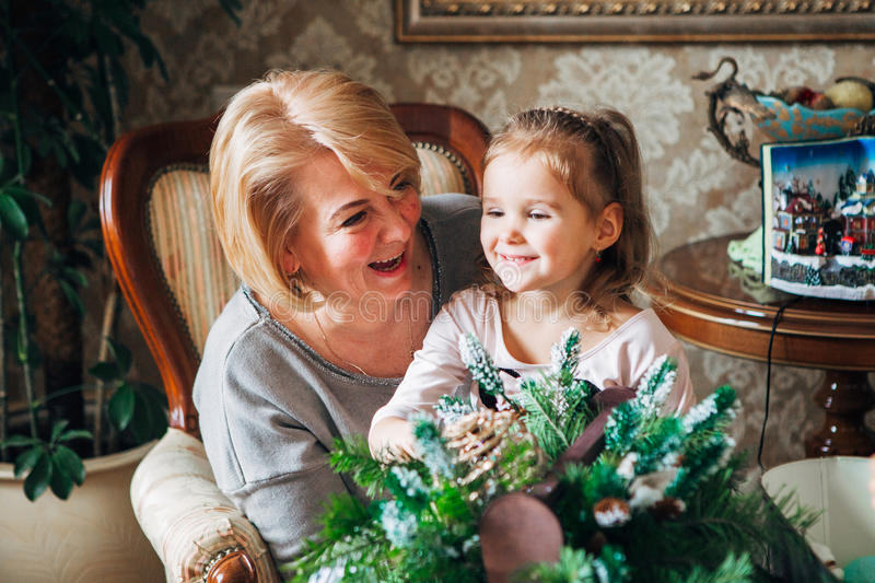 Grandmother with child preparing for Christmas. Grandma laughing along with her granddaughter,preparing for the new year stock photos