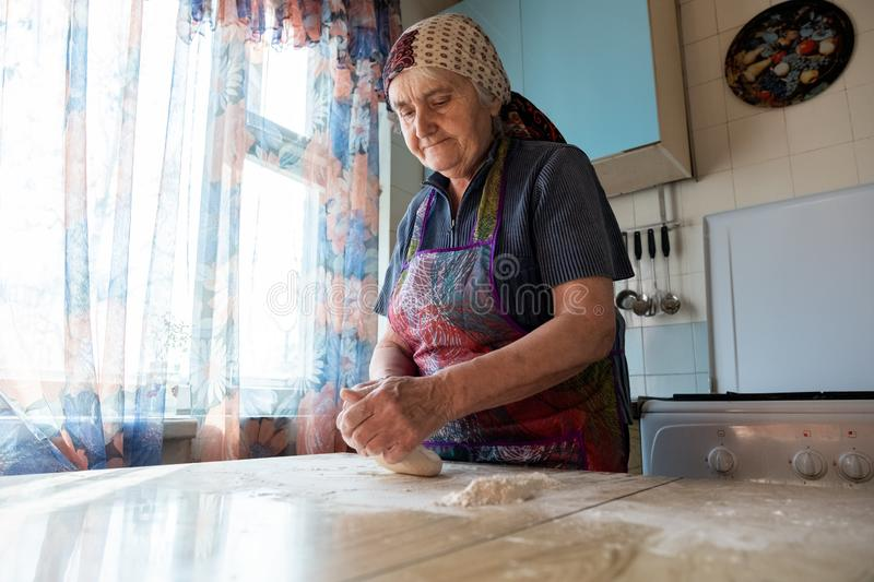 grandmother cooking bakery products, fresh bread, tasty pie royalty free stock image
