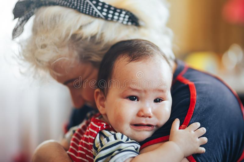 Grandmother cradling crying infant baby girl looking at camera.  stock images