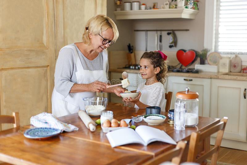 Grandmother and cute curly granddaughter prepare together in the kitchen. stock photo