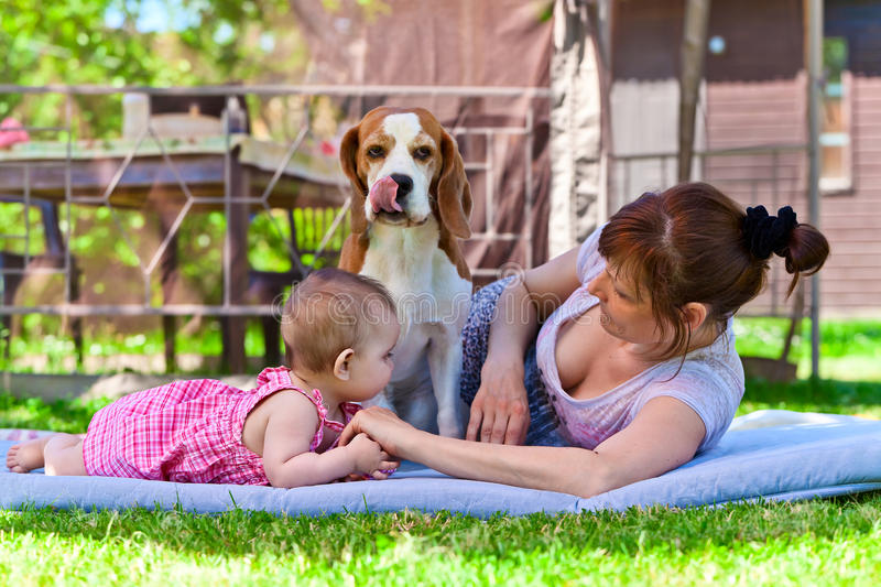 Grandmother with dog and granddaughter. In garden royalty free stock photo