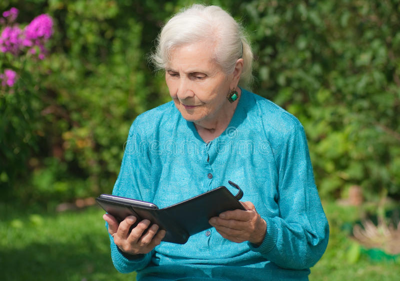 A grandmother with an e-book. The grandmother with an e-book stock photography